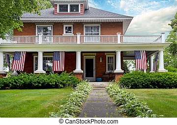 old brick home with American flags - American flags...