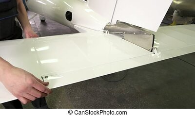 Worker and tail of airplane. White shiny metal. Aircraft...