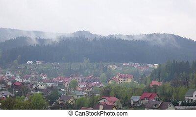 Time lapse of cloudy morning in small town in mountains