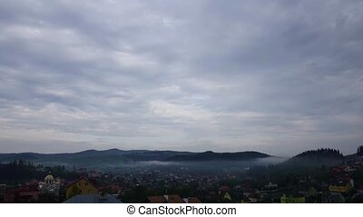 Morning fog in mountains village Time lapse of cloudy morning