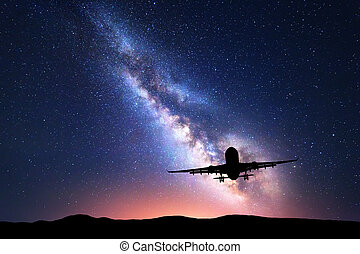 Milky Way and silhouette of a airplane. Landscape with...