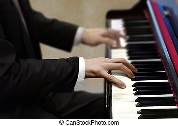 Man in black suit playing piano