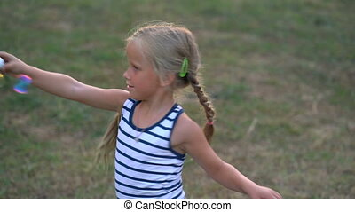 Little girl playing with bubbles in the park on a sunset -...