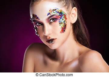 Gorgeous model with colorful creative makeup in studio...