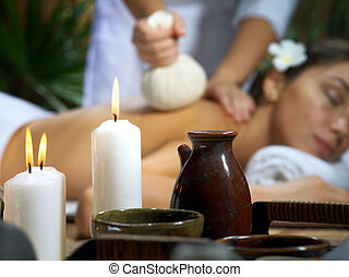 portrait of young beautiful woman in spa environment. focused on candles.