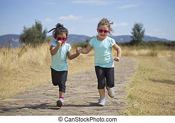 Lovely sisters running along path in countryside - Portrait...