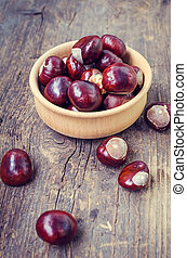 Fresh chestnuts on the old wooden table - Fresh chestnuts in...