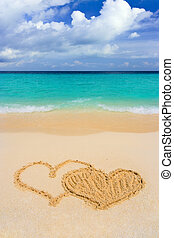 Drawing connected hearts on beach, love concept