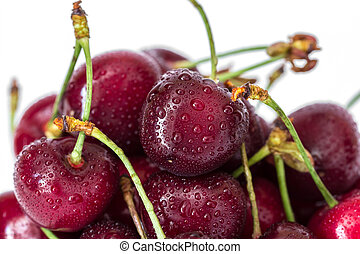 Pile of red cherries on a stem with water drops macro