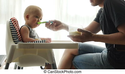 Father feeding cute baby at home - Father feeding cute baby...
