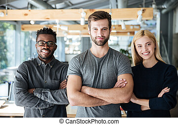 Smiling young colleagues standing with arms crossed