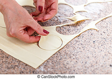 Round shaped biscuits - Woman hand cutting out round shaped...