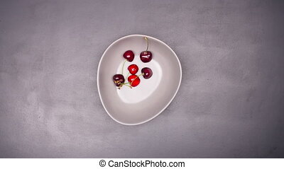 Fresh cherries in bowl on table stop motion - Fresh cherries...