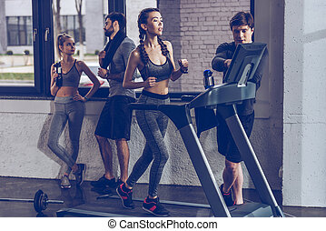 athletic young sportswoman running on treadmill at the gym,...