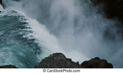 Close-up view of the beautiful blue water falls down from mountain. Scenic landscape of Gullfoss waterfall in Iceland.