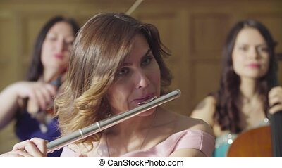 Portrait of young woman playing a flute - Close up portrait...