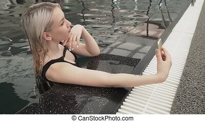 Beautiful young girl doing selfie on iphone in pool stock footage video