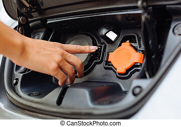 Delicate female hand being about to charge an e car - Car...