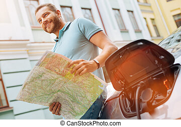 Bearded man examining a map while charging the car - Happy...