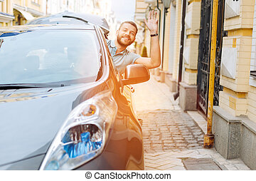 Handsome bearded young man waving from his car - Hey there....