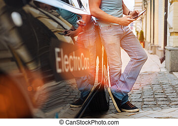 Well-built man checking his tablet near electric car - Busy...