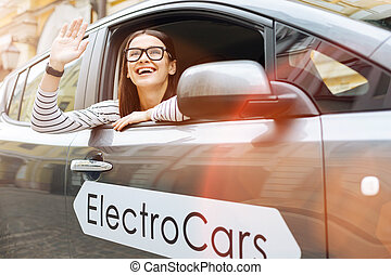 Smiling woman waving at familiar passer-by from car - Happy...