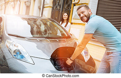 Smiling man unplugging the charger from the car - Ready to...