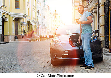 Well-built man charging e-vehicle and having coffee -...