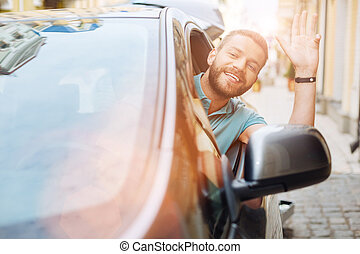 Man leaning out of the car window and greeting someone -...