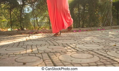 Girl in Coral Dress Steps Ahead on Pavement - long-legged...