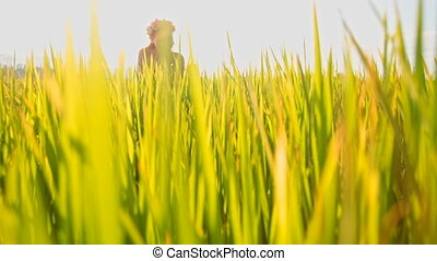 View of Girl Sitting in Field Through Green Stems - view of...