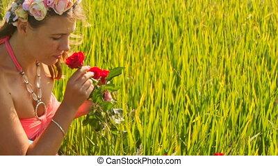 Closeup Girl Squats in Green Grass Smells Roses