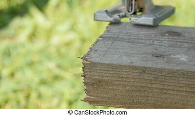 An electric jigsaw cuts the board. - A man saws a board with...