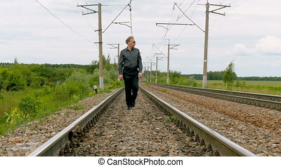 A man walks by rail. - A man in a business suit wearing...