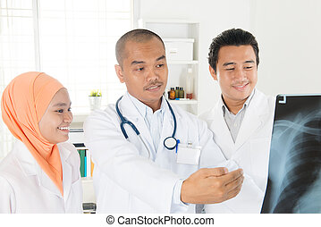 Medical team checking on x-ray image - Doctors looking at...