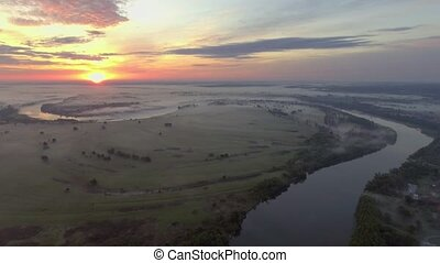 Aerial view of the dawn over the river in the fog