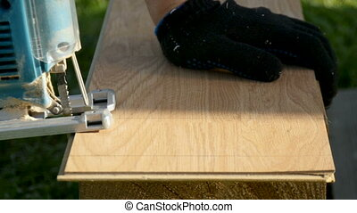 A man saws a laminate with an electric jigsaw. close-up - A...