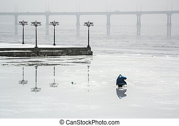 The fisherman is fishing on the ice of a frozen river in an...
