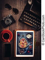Food blog concept with pancakes on tablet pc on wooden desk