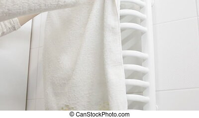 Woman put the white towel on the hanger