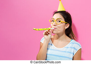 Young woman with noisemaker - Young woman with party hat...