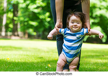 Baby boy learning to walk outside with the help of his...