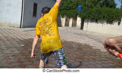 man is showered with water from a hose.