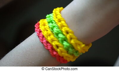 Woven multi-colored bracelets on the arm.
