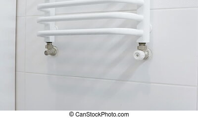 Woman put the white towel on the hanger in the bathroom