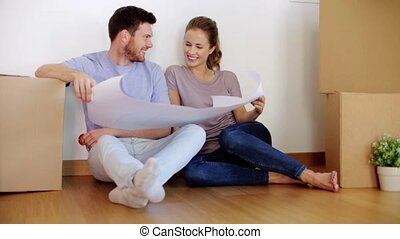 happy couple with blueprint at new home - real estate,...