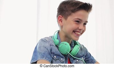 boy with headphones having video chat on laptop -...