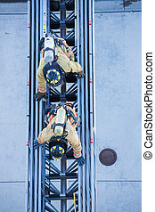 Firefighter training entering and exiting a building on a truck ladder overhead view
