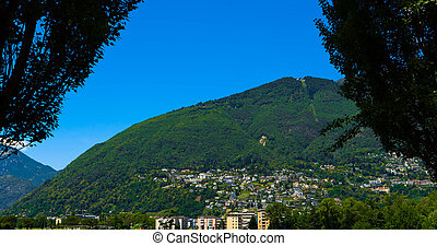 Scenic mountain with a forest and houses in the city of Ascona, Switzerland.