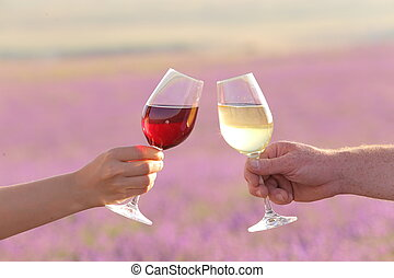 Two hands toasting wine glasses.